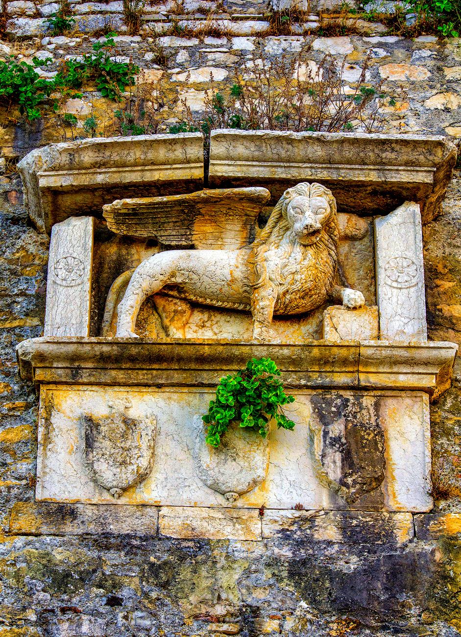Το λιοντάρι του αντικρημνού (Contrascarpa) της Τάφρου (Fossa), κάτω από την εκκλησία της Παναγίας Μανδρακίνας. Τα τρία στέμματα που περιλαμβάνονται στο σύνολο είναι σύμφωνα με τoυς Rusconi & Gerola αυτά του βάιλου Zaccaria Morosini (1554-56) και των δύο συμβούλων(Consiglieri) Leone Mocenigo (1555-57) & Giovanni Zani (1555-57).