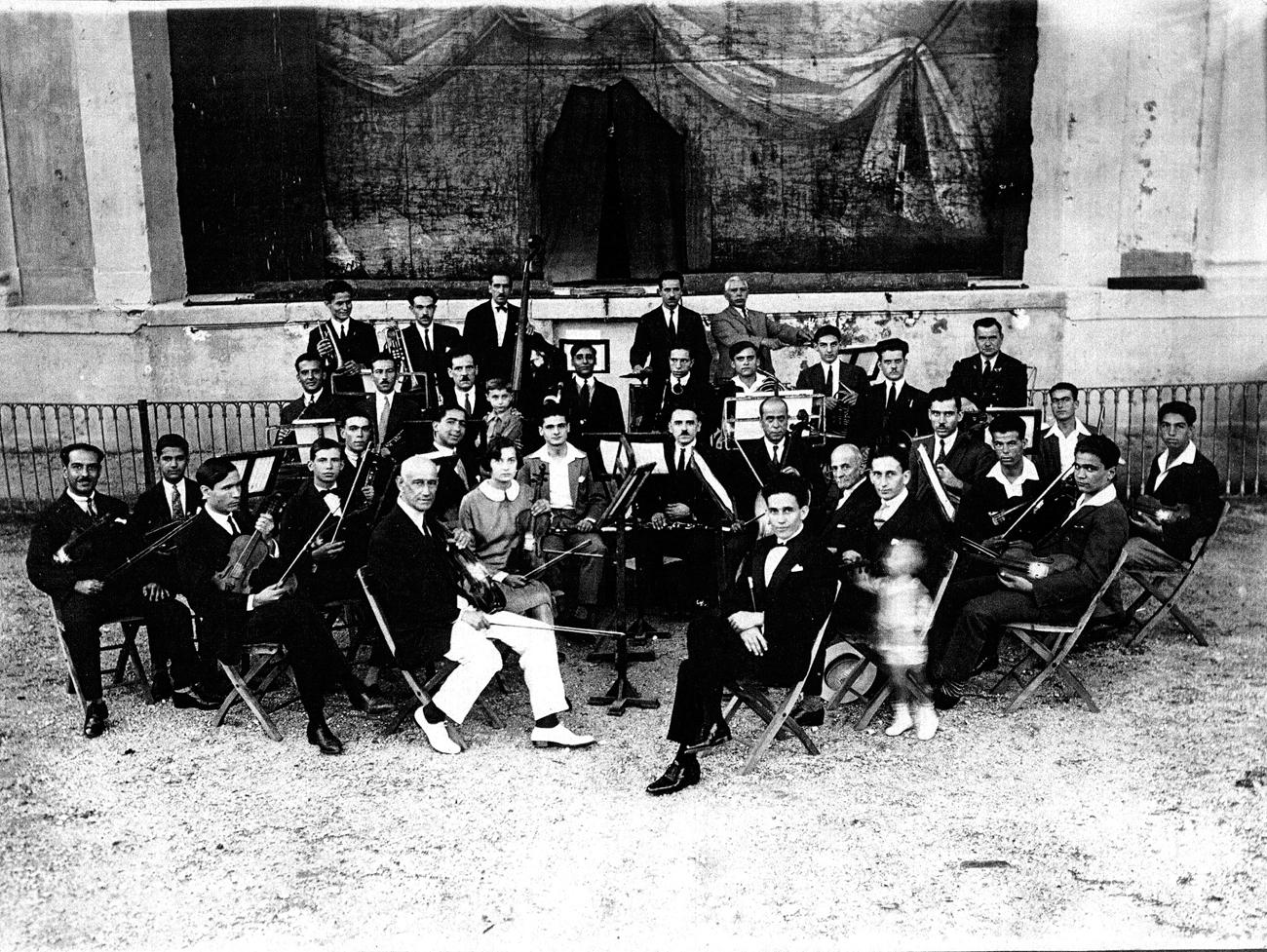 """Αύγουστος 1931: Δοκιμή ορχήστρας για το ανέβασμα της όπερας του Γεράσιμου Ρομποτή """"Η κόρη του φονιά"""". Σε πρώτο πλάνο δεξιά ο συνθέτης."""
