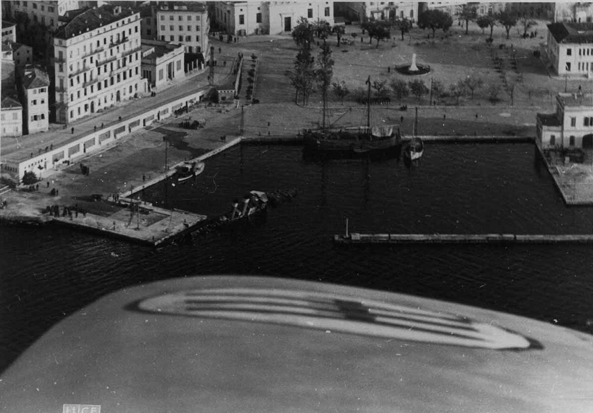 Ιταλικό αεροσκάφος υπερίπταται του Λιμανιού (διακρίνεται μισοβουλιαγμένη η Προύσσα στο Καφέ Γυαλί)