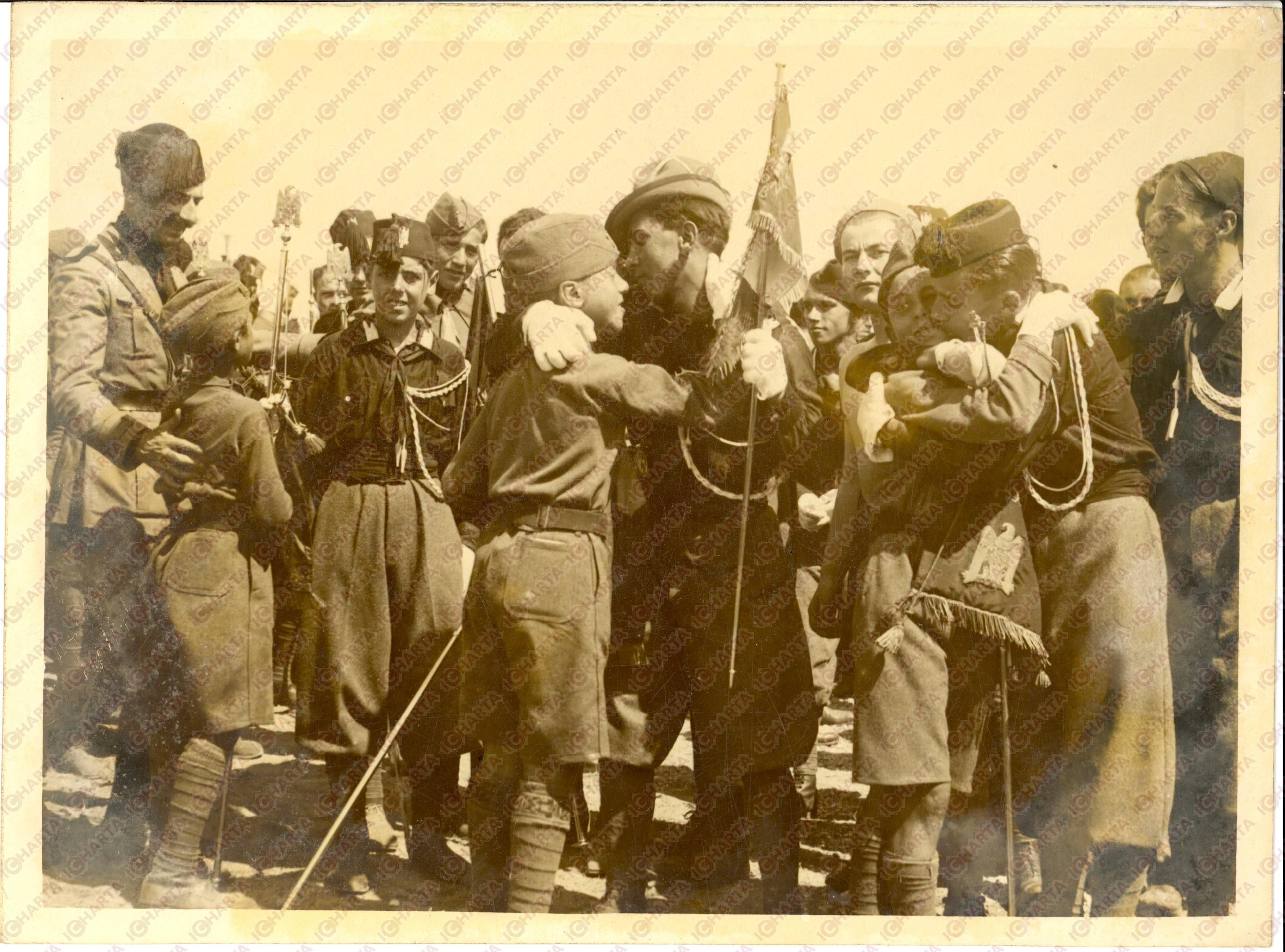 1936. «Αδελφικό αγκάλιασμα μεταξύ μελών Φασιστικής Νεολαίας του στρατοπέδου «DUX» και μελών Φασιστικής Νεολαίας Εξωτερικού του στρατοπέδου «Μουσολίνι», κοντά στη Ρώμη».